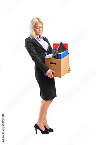 Fired businesswoman in a suit carrying a box of personal items
