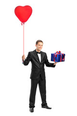 Man holding a red heart shaped balloon and a gift