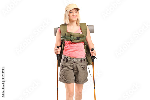 A smiling woman with backpack and hiking poles posing