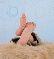 close-up of a child's feet over  furry blanket