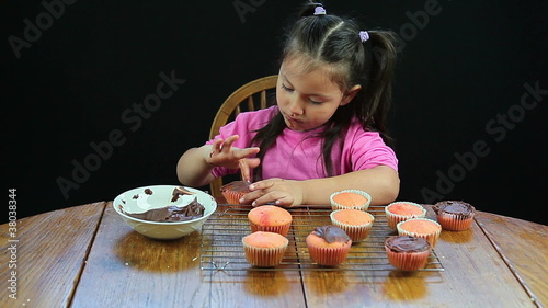 Child smearing frosting on cupcakes