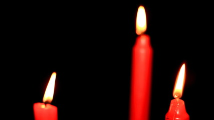 Three red candles on black background