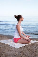 Young beautiful woman doing yoga near the sea alone
