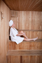 Middle aged woman enjoying a hot sauna