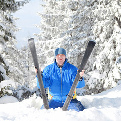 Happy man with ski in the winter landscape