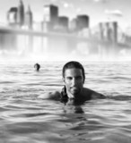 Man in ocean with city background