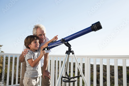 Grandfather and grandson using telescope on beach balcony