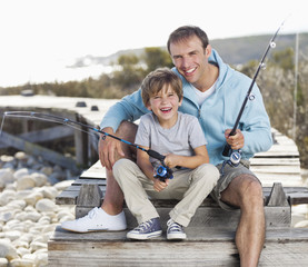 Portrait of father and son fishing on dock