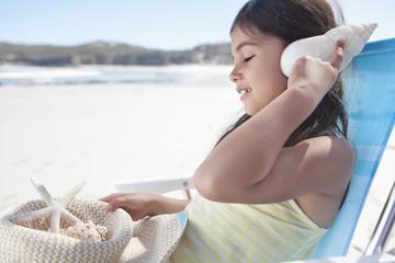 Girl holding seashell to ear on beach