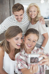 Multi-generation family taking self-portrait with digital camera