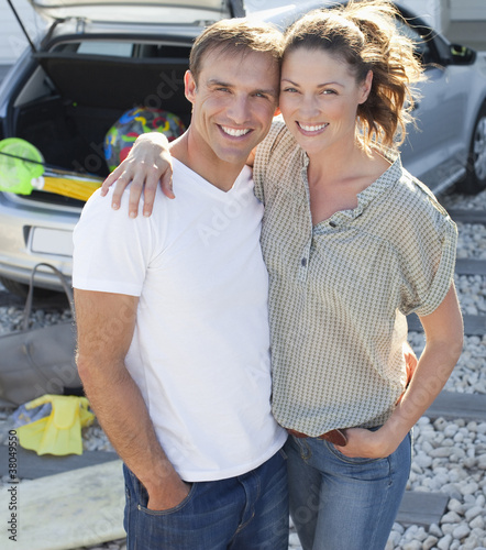 Portrait of smiling couple in driveway preparing for beach trip