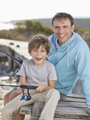 Portrait of smiling father and son holding fishing rod