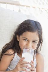 Portrait of smiling girl drinking milk in hammock