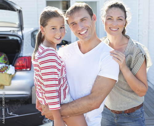 Portrait of smiling parents with daughter in driveway
