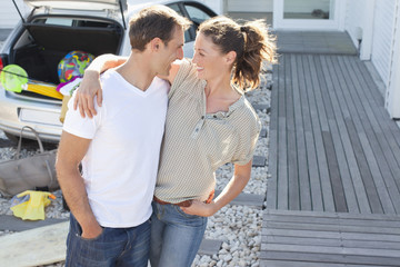 Happy couple hugging in driveway