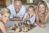 Portrait of smiling family playing chess on floor
