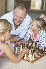Father and daughters playing chess on floor