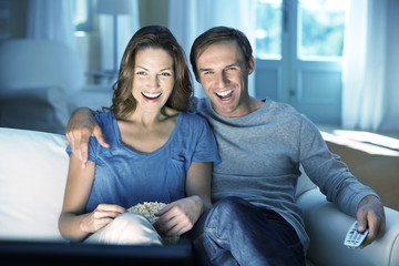 Smiling couple watching TV on sofa
