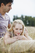 Smiling woman laying on man?s lap in rural field