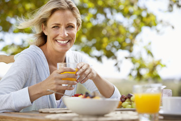 Portrait of smiling woman eating breakfast outdoors