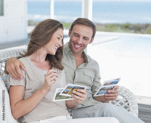 Smiling couple writing postcards on patio overlooking ocean