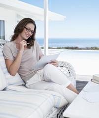 Smiling woman looking at paperwork on patio overlooking ocean
