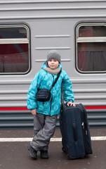A boy with a travel bag near a train