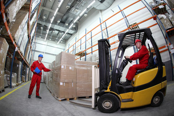 two workers  loading pallets  with  forklift truck