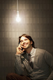 Smiling businessman sitting under illuminated light bulb