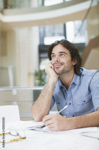 Businessman daydreaming at desk in office