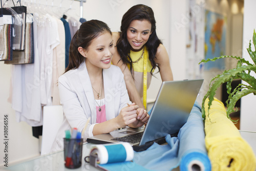 Fashion designers using laptop in office