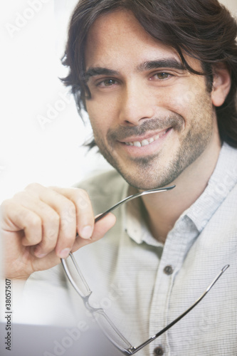Portrait of smiling businessman holding eyeglasses