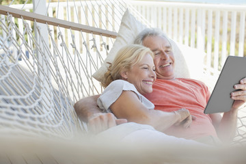 Happy senior couple laying in hammock with digital tablet