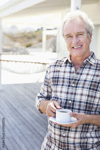 Portrait of smiling senior man drinking coffee on patio