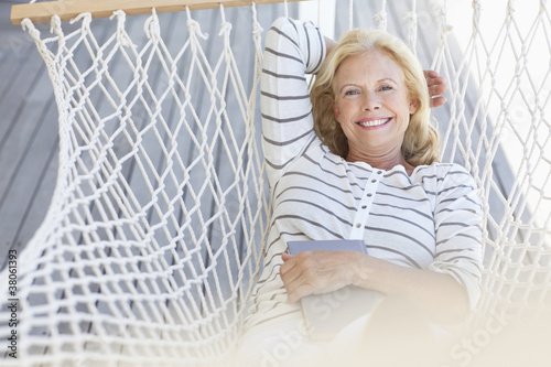 Portrait of smiling senior woman laying in hammock with book