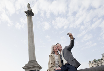Couple taking self-portrait with digital camera under monument