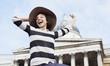 Exuberant woman in hat below historical landmark in London