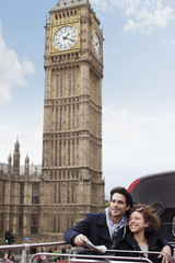 Couple riding double decker bus past Big Ben clocktower in London
