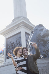Couple with British flag taking self-portrait with digital camera under monument in London
