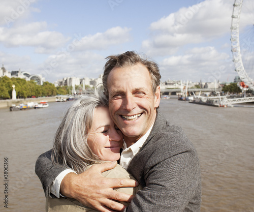Smiling couple hugging along the Thames river in London