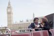 Couple with digital camera riding double decker bus near Big Ben clocktower in London