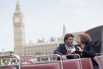 Couple with digital camera riding double decker bus near Big Ben clocktower in London