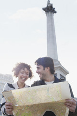 Happy couple with map below monument