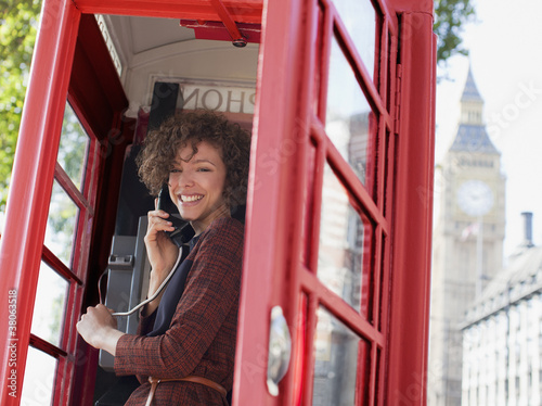 Portrait of smiling woman in telephone booth in London