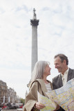 Couple with map smiling face to face under monument
