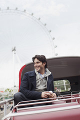 Happy man riding double decker bus in London
