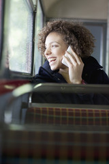 Happy woman talking on cell phone on bus