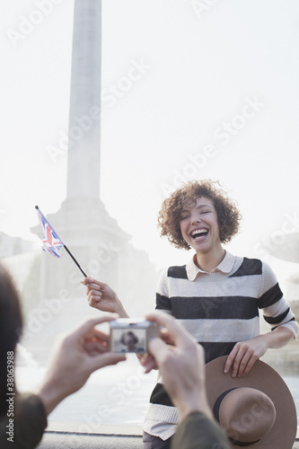 Man with digital camera taking photograph of happy woman with British flag in front of fountain