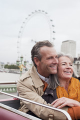 Smiling senior couple on double decker bus in London