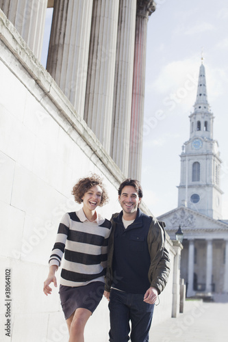 Happy couple walking along sunny urban buildings